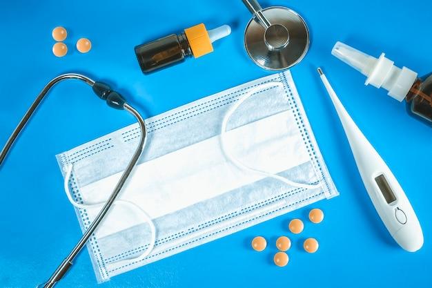 Behandeling van verkoudheid en griep. ziektedag en medisch verlofconcept. verschillende medicijnen, een thermometer, sprays van een verstopte neus op blauwe achtergrond, traditionele geneeskunde en griepconcept. medicijn plat leggen.