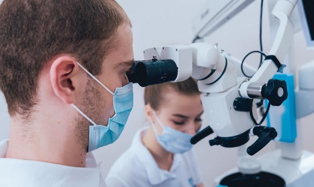Behandeling van wortelkanalen onder een microscoop, werk met een assistent.
