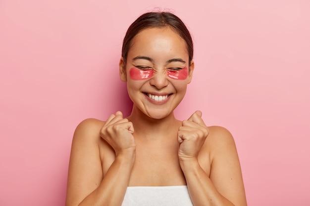 Behandelingen voor het gebied onder de ogen, huidverzorging. gelukkig tevreden aziatische vrouw heeft cosmetische pleisters onder de ogen om wallen te minimaliseren, balde vuisten van vreugde en plezier, heeft schoonheidsprocedures thuis