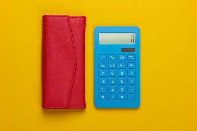 Beheer het gezinsbudget. boodschappen kosten. blauwe calculator met rode leerportefeuille op gele achtergrond. bovenaanzicht