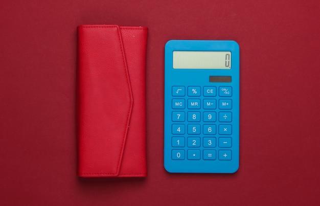 Beheer het gezinsbudget. boodschappen kosten. blauwe calculator met rode leerportefeuille op rood oppervlak. bovenaanzicht