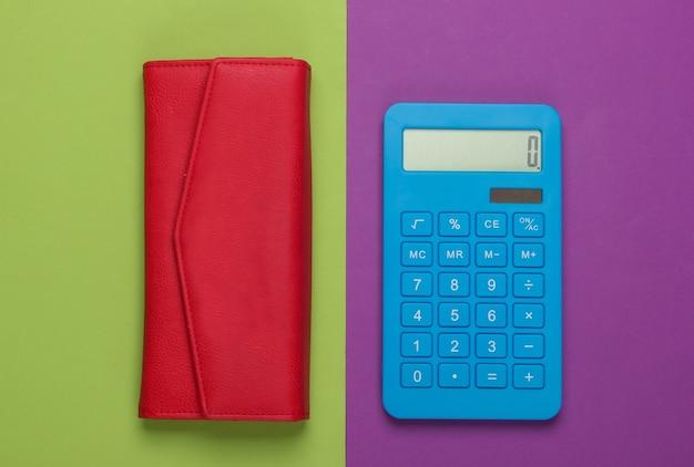 Beheer het gezinsbudget. boodschappen kosten. blauwe rekenmachine met rode lederen portemonnee op paars groen oppervlak. bovenaanzicht