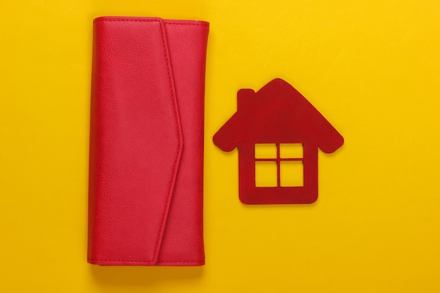 Beheer van het gezinsbudget. beeldje van een huis met portemonnee op geel
