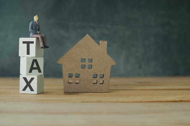 Beheer van onroerend goed belasting concept, belasting laatste op houten gestapeld met thuis model