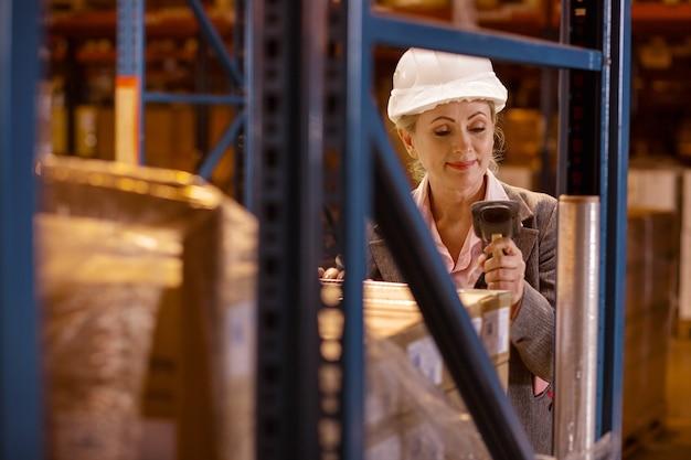 Beheerder. opgetogen aardige vrouw die een scanner vasthoudt terwijl ze goederen in de dozen controleert