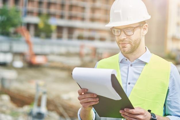 Beheersing van het project jonge gefocuste civiel ingenieur of bouwsupervisor die een helm draagt