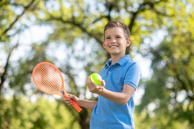 Behendigheid, vertrouwen. zelfverzekerde vriendelijke glimlachende schoolgaande jongen in blauwe t-shirt met racket en tennisbal in het park op zomerdag