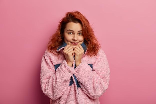 Behoorlijk blij roodharig meisje voelt troost in het dragen van een nieuwe roze warme jas, kijkt direct naar de camera, heeft kuiltjes op de wangen