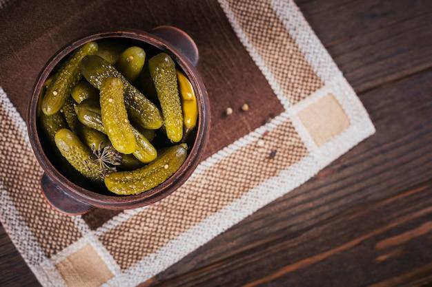 Behoud van ingemaakte komkommers, kruiden en knoflook op een donkere houten tafel. gezond gefermenteerd voedsel. thuis ingeblikte groenten.