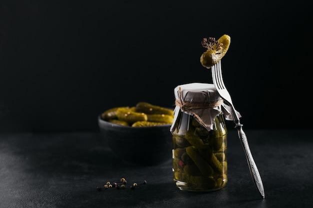 Behoud van ingemaakte komkommers, kruiden en knoflook op een donkere tafel. gezond gefermenteerd voedsel. thuis ingeblikte groenten.