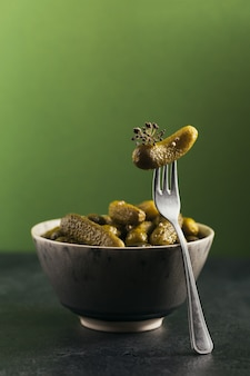 Behoud van ingemaakte komkommers, kruiden en knoflook op een groene achtergrond. gezond gefermenteerd voedsel. thuis ingeblikte groenten.