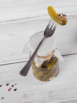 Behoud van ingemaakte komkommers, kruiden en knoflook op een witte houten tafel. gezond gefermenteerd voedsel. thuis ingeblikte groenten.