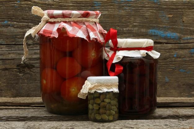 Behouden. pot met aardbeienjam, ingelegde tomaten en kappertjes op houten