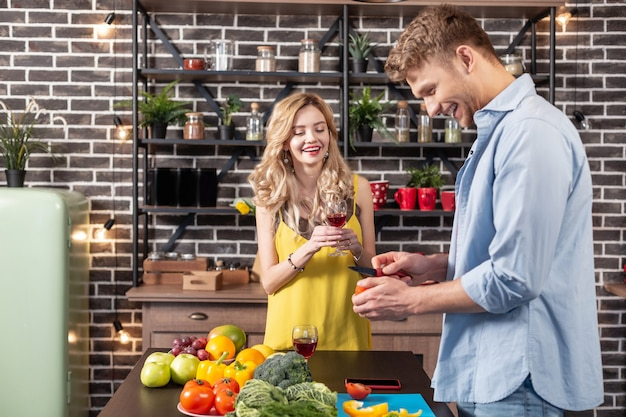 Behulpzame echtgenoot. gelukkige vrouw kijkt toe hoe haar behulpzame man het diner kookt voor hun romantische avond