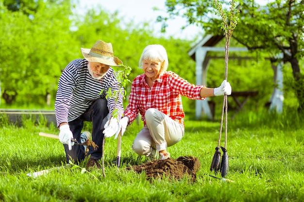 Behulpzame echtgenoot. liefdevolle gepensioneerde echtgenoot helpt zijn mooie vrouw met het graven van grond voordat ze bomen plant