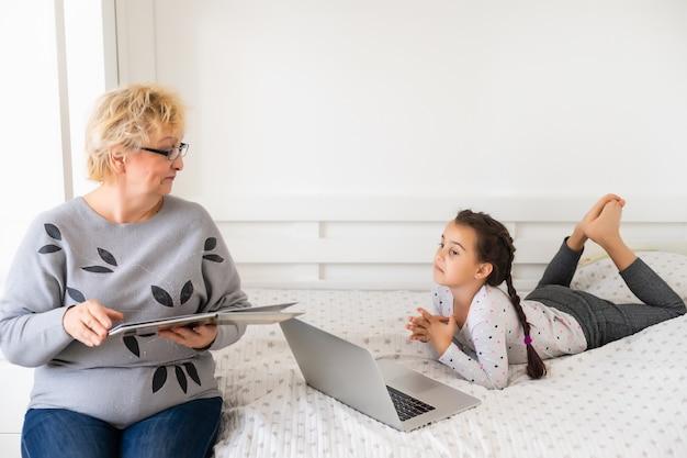 Behulpzame oma. behulpzame liefhebbende oma die haar schattige kleindochter helpt bij het maken van huiswerk