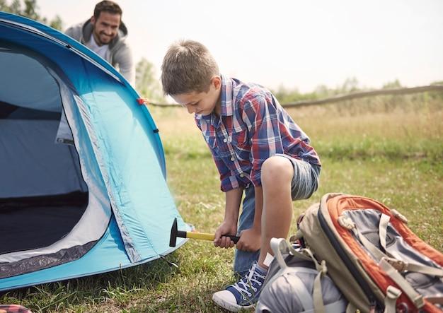 Behulpzame zoon op de camping met zijn vader