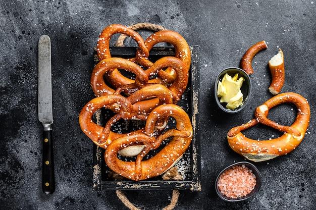Beierse gebakken gezouten pretzels in een houten dienblad. zwarte achtergrond. bovenaanzicht.