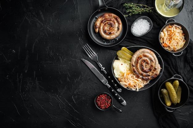 Beierse gebakken worstjes op zuurkool, op zwarte achtergrond, bovenaanzicht plat lag, met ruimte voor tekst copyspace