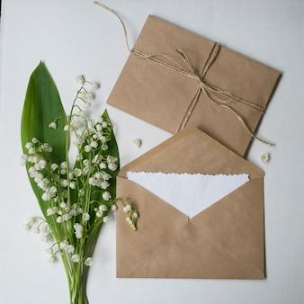 Beige ambachtelijke enveloppen, witte blanco notitie-kaart en boeket van lelietje-van-dalen.