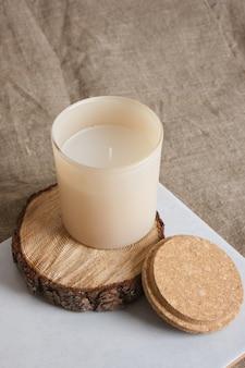 Beige aromakaars op een houten podium van een zaag die uit een boom is gesneden. natuurlijke kaarsen voor aromatherapie kopieer ruimte