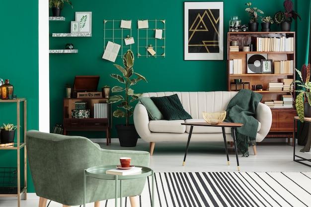 Beige bank en groene fauteuil in elegant woonkamerinterieur met ficus en poster