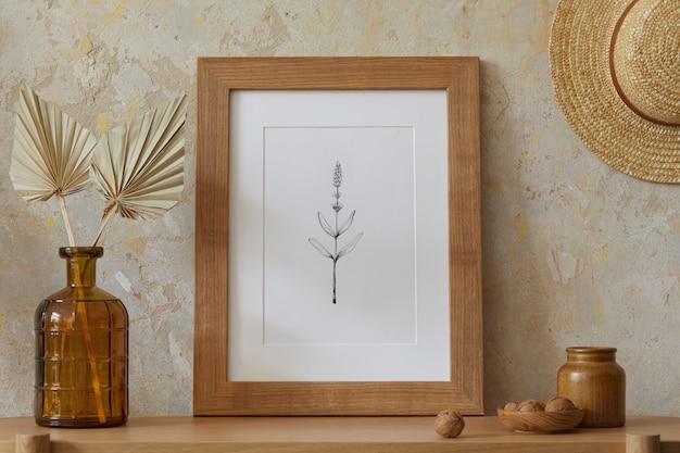Beige boho interieur van woonkamer met mock up posterframe, elegante accessoires, gedroogde bloemen in vaas, houten console en hangende hoed in stijlvol interieur.
