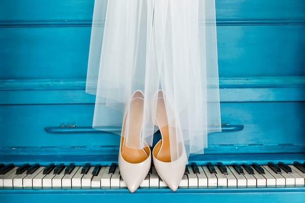 Beige bruidsschoenen staan op de piano bedekt met een witte sluier