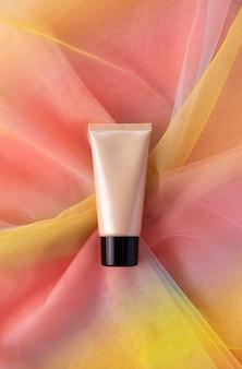 Beige buis voor schoonheidsproduct op kleurrijke regenboog organza stof. cc bb cream tonale foundation make-up mockup. huidverzorging hygiëne concept