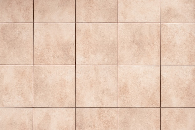 Beige ceramiektegelachtergrond op de vloer