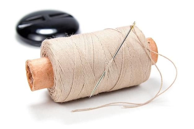 Beige draad op een kartonnen spoel met een naald en knoop op witte achtergrond