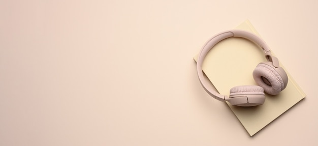 Beige draadloze hoofdtelefoons en een gesloten blocnote. bovenaanzicht en plaats voor een inscriptie