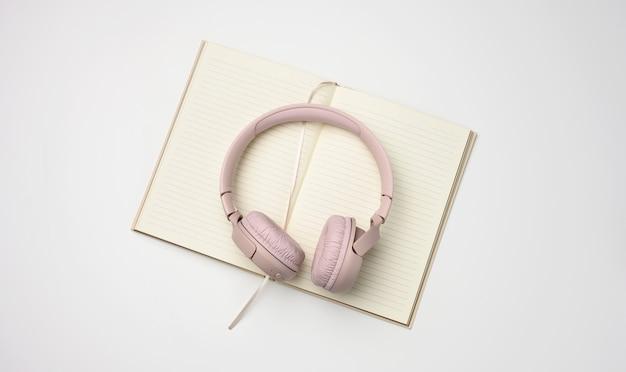 Beige draadloze koptelefoon en een open kladblok op een witte achtergrond. bovenaanzicht