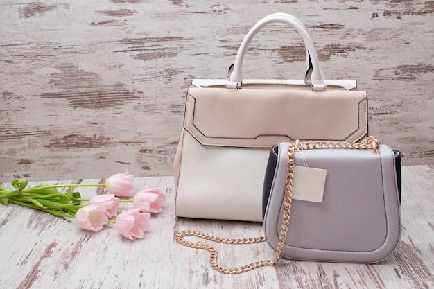 Beige en grijze zakken op houten, roze tulpen. in de mode .
