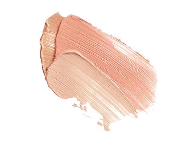 Beige en roze concealer penseelstreken geïsoleerd op wit
