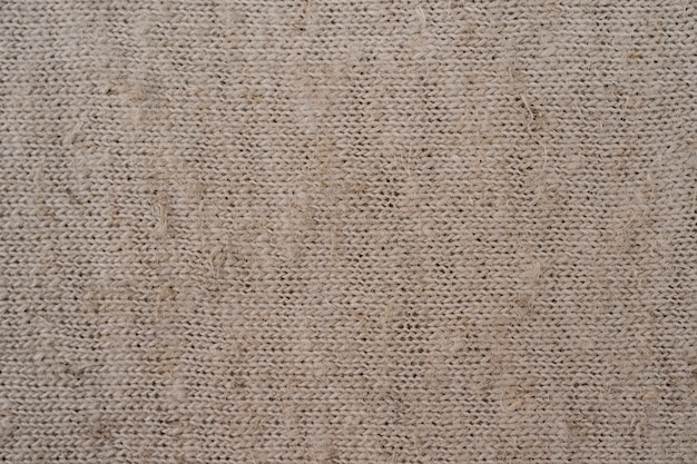 Beige grofkorrelige stof die als ontwerpachtergrond kan worden gebruikt textuur van natuurlijke linnen stof