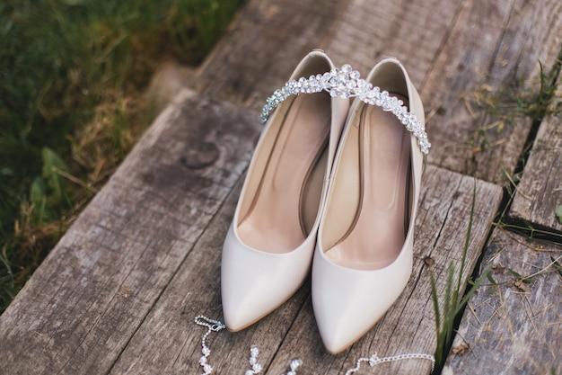 Beige hoge hakken pumps schoenen en bruiloft sieraden liggen op een vintage houten tafel