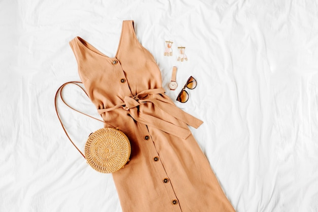 Beige jurk met bamboe tas en accessoires op wit bed. stijlvolle herfst- of zomeroutfit voor dames. trendy kleding. plat lag, bovenaanzicht.
