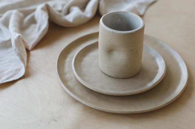 Beige keramische plaat op een houten tafelblad. minimalistisch handgemaakt keramisch servies en aardewerk