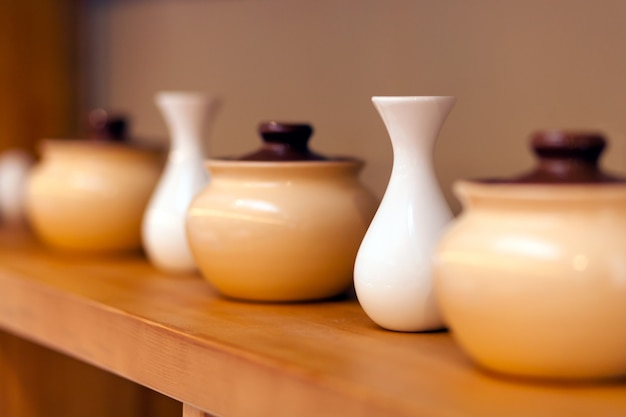 Beige keramische potten en witte kleine vazen