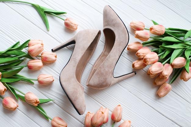 Beige kleur naakt vrouwen schoenen met bloemen op witte houten achtergrond bovenaanzicht