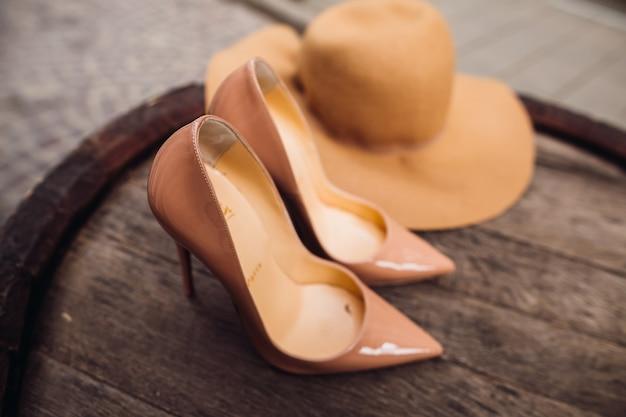 Beige luis vuitton schoenen en hoed liggen op het vat