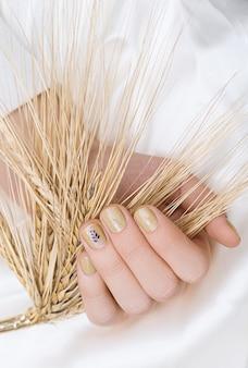 Beige nageldesign. vrouwelijke hand met glitter manicure.
