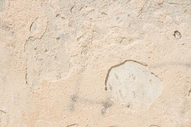 Beige ouderwetse gepleisterde muur