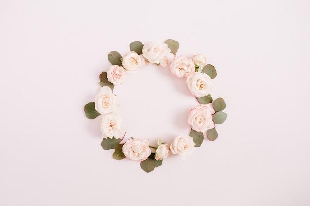 Beige rozen, eucalyptus takken op bleke pastel roze achtergrond. plat lag, bovenaanzicht. floral textuur achtergrond.