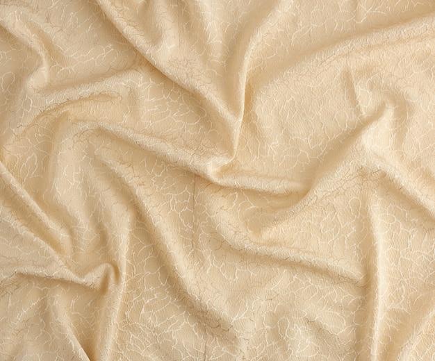 Beige satijnen textielstof met borduurelementen, stuk canvas voor het naaien van gordijnen en zo, full frame