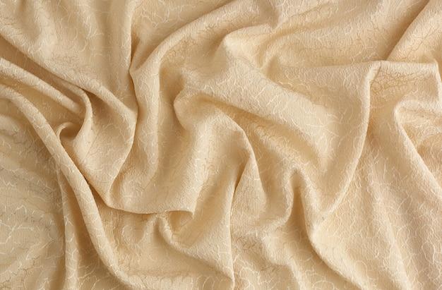 Beige satijnen textielstof met borduurelementen, stuk canvas voor het naaien van gordijnen