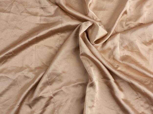 Beige satijnen textielstof, stuk canvas voor het naaien van gordijnen en zo