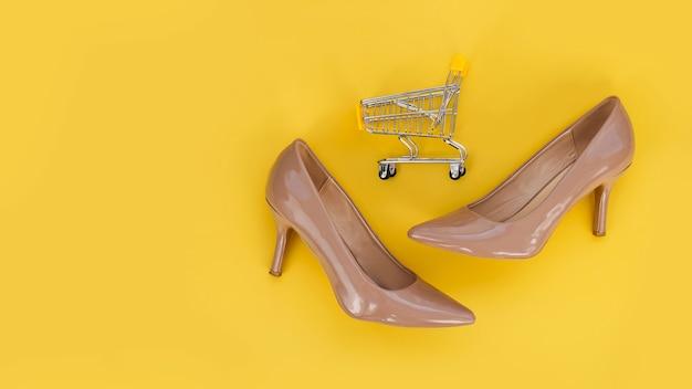 Beige schoenen en een winkelwagentje op een gele achtergrond