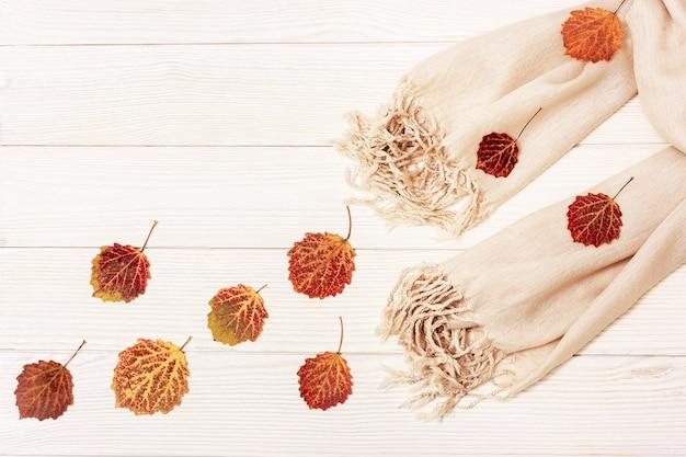 Beige sjaal en natuurlijke rode bladeren van espboom